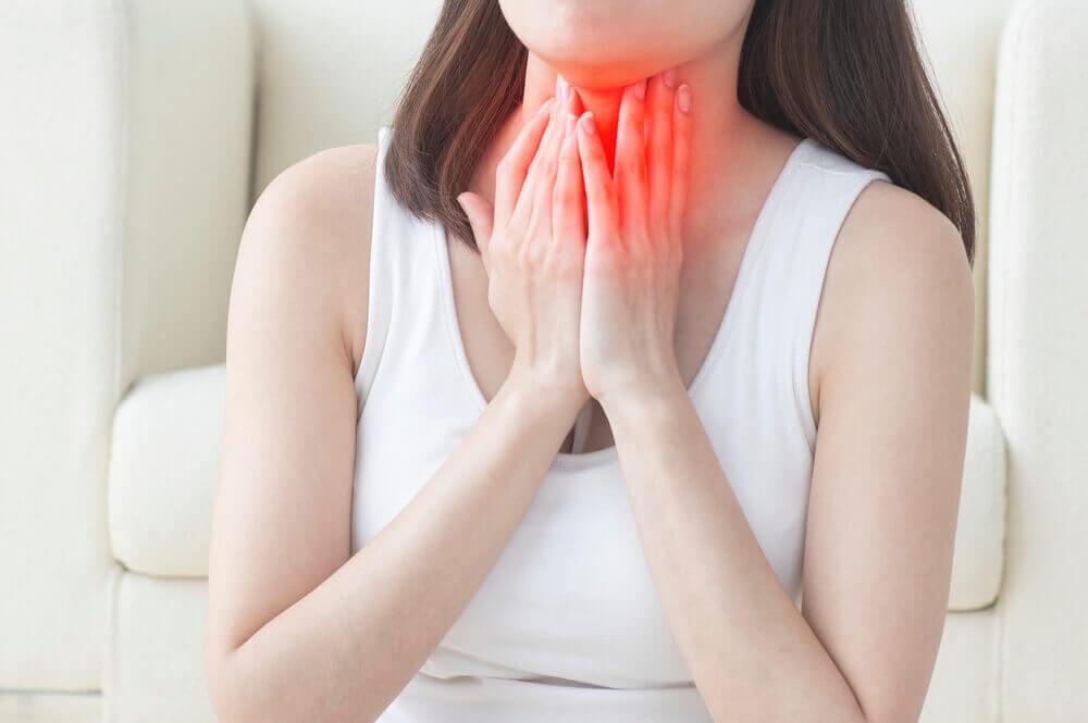 kobieta dotykająca gardła