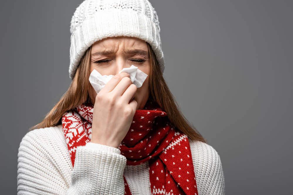 kobieta przykładająca chusteczkę do nosa