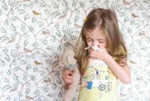 mała dziewczynka przykłada chusteczkę do nosa